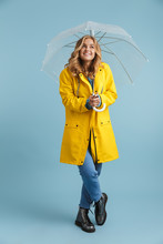Full Length Image Of European Woman 20s Wearing Yellow Raincoat Standing Under Transparent Umbrella, Isolated Over Blue Background