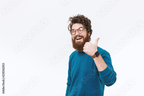 Fototapeta Cheerful smiling bearded hipster man wearing glasses and showing thumbs up obraz