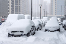 Many Cars Parked In The Business District Of The City During A Snow Storm