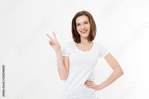 Fototapeta Happy young caucasian girl showing victory sign isolated on white background. Copy space. Template and blank summer t shirt. obraz na płótnie