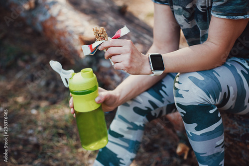 Sporty Woman Eating Protein Bar and drinking an amino acid cocktail. Woman in military-colored clothing in forest