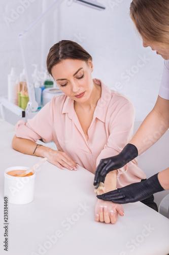 Fotografie, Tablou  Dark-haired woman watching her master making wax depilation