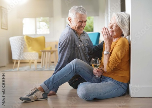 Photo  Relaxed senior couple sitting on floor in modern home with glass of wine
