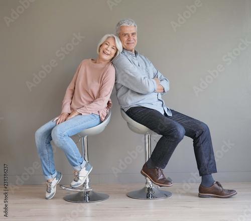 Obraz  Happy senior couple sitting on bar stools on grey backgound - fototapety do salonu