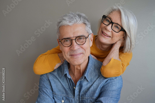 Cuadros en Lienzo Portrait of relaxed fun senior couple wearing glasses on background