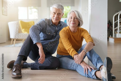 Photographie  Relaxed senior couple sitting on floor in modern home looking at camera