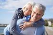 canvas print picture -  Fun loving senior couple piggyback riding outdoors