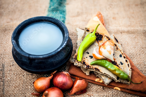 Valokuvatapetti Close up of meal or lunch of villager or a typical farmer on gunny bag's background consisting of pearl millet's roti or chapati or bajra or bajri ki roti with some onions and chilies, buttermilk