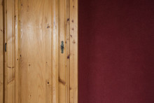 Brown Wooden Closet Doors Close Up With Red Bordeaux Wall