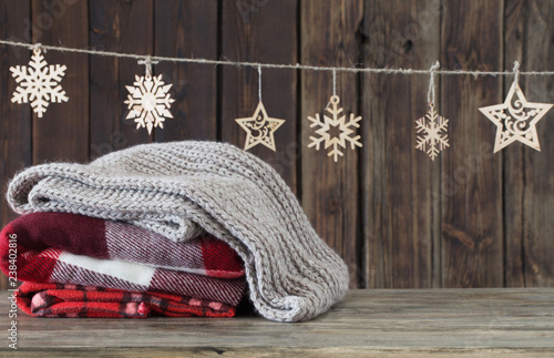 Obraz stack of plaids and Christmas decorations on wooden background - fototapety do salonu