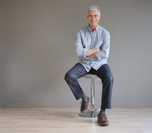 Full Length Casual Senior Man Sitting On Stool On Gray Background