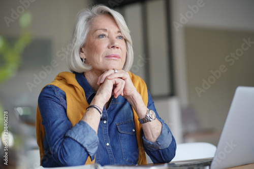 Beautiful senior woman looking pensive at home with laptop Wallpaper Mural