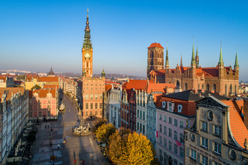 Poland. Gdansk Old City skyline with medieval Gothic Saint Mary Cathedral, city hall with clock tower, Dluga street, Artus Court and Neptune statue with fountain. Aerial view in sunrise light in fall