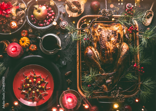 Fototapeta Christmas dinner table with whole roasted turkey, stuffed with dried fruits served in roasting pan with sauce,red plates, cutlery, decoration and burning candles,  top view. Traditional Christmas food obraz