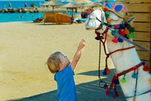 Cute Little Boy Feeding Camel On The Beach. Holidays On The Sea. Copy Space