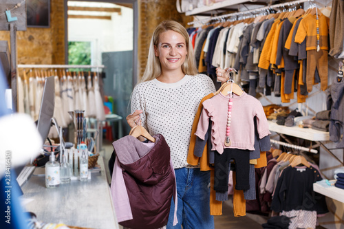 66590a381 Woman holding hanger with baby clothes in showroom - Buy this stock ...