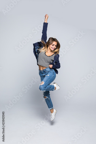 Full length portrait of a joyful young woman jumping and celebrating over gray background Wall mural