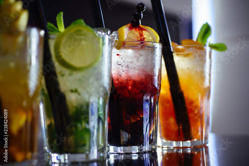 Poster Cocktail Alcohol addiction. Cocktail drinks served in glasses with drinking straws. Iced drinks in cocktail glasses. Alcoholic mixed drinks with ice. Juicy alcohol beverages on bar counter. Drinking all day