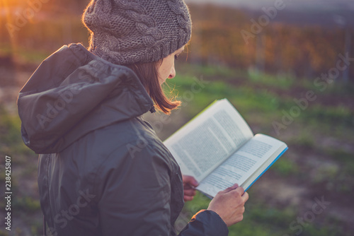 Deurstickers girl with jacket and hoodie reading book at park in autumn sunset light
