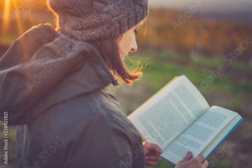 Deurstickers girl reading book at park in autumn sunset light