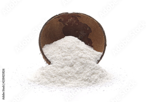 Pile of shredded coconut meat in coconut shell isolated on white background
