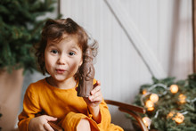 Cute Curly Toddler Girl Wearing Mustard Linen Dress In Studio Near Christmas Tree.