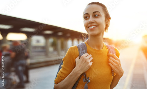 portrait of a young woman traveler with small backpack on the railway stantion Fotobehang