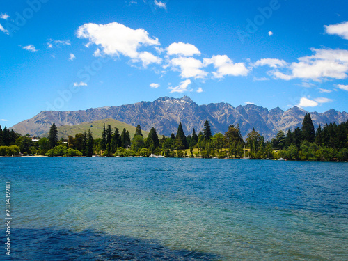 Fotografia  Clear blue water in front of the mountains
