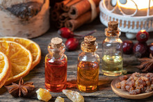 Christmas Collection Of Essential Oils With Frankincense, Myrrh, Cinnamon, Rose Hips And Orange Slices