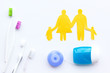 Daily oral hygiene for family. Toothbrush, dental floss and family figures on white background top view