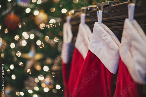 Fototapeta Christmas stockings hanging on mantle near tree