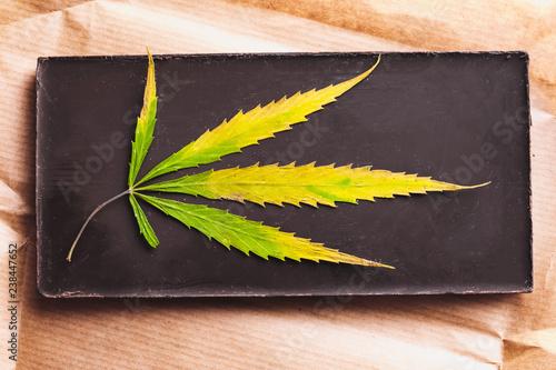 Fotografie, Obraz  Marijuana leaf with edible dark chocolate block and cannabis brownie with ganja
