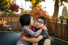 Sister Kissing Her Brother On A Trampoline