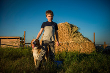 Portrait Of Boy With Dog Standing In Field