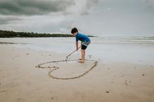 Boy Making Heart Shape On Sand At Beach