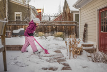 Side View Of Girl Removing Snow From Backyard