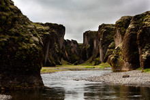 Scenic View Of River Flowing Amidst Rock Formations Against Cloudy Sky