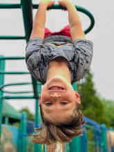 Close-up Portrait Of Cute Smiling Boy Hanging Upside Down On Jungle Gym Against Sky At Park