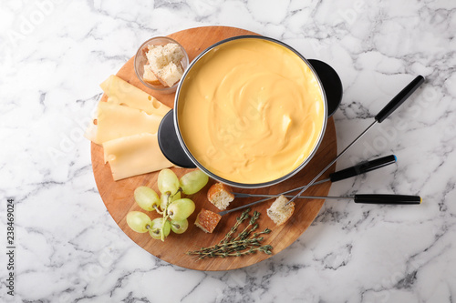 Flat lay composition with pot of delicious cheese fondue on marble table