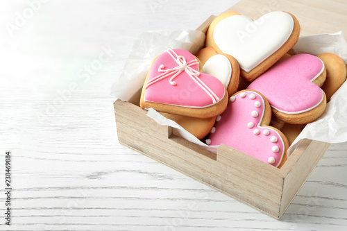 Fototapeta Decorated heart shaped cookies in wooden box on table. Space for text obraz