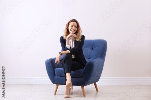 Fényképezés  Beautiful young woman sitting in armchair indoors