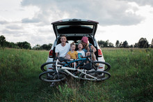 Happy Family With Bicycles Sit...