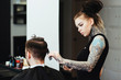 Side view of female hairdresser cutting male customer's hair in salon
