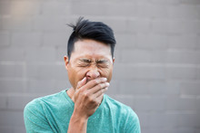 Close-up Of Man With Hands Covering Mouth While Yawning Against Wall