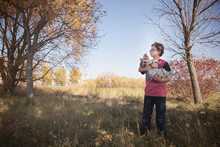 Boy With His Pet Dog Standing In Grassy Field At Park
