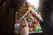 Cropped Hand Of Girl Decorating Gingerbread House With Candies On Table At Home