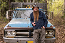 Portrait Of Bearded Man Leaning On Old Pickup Truck In Forest