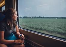 Teenage Girl Looking Through Window While Traveling In Train