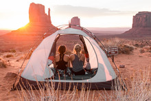 Rear View Of Friends Sitting In Tent Against Sky At Monument Valley Tribal Park During Sunset