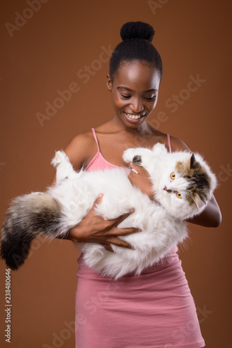 Fotografie, Obraz  Young beautiful African Zulu woman holding cat while smiling